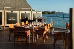 Exterior view of outdoor family table at The Terraces Restaurant with ocean view