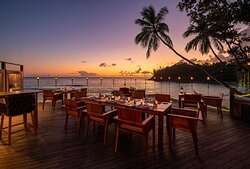Exterior view of outdoor family table setup at The Terraces Restaurant with ocean view at sunset