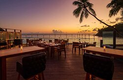 Exterior view over outdoor seating at The Terraces Restaurant with ocean view at sunset