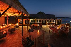 Exterior view of outdoor seating and bar area at The Terraces Restaurant with ocean view at night