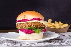 """Burger """"Bombay"""" Hamburguesa de lentejas empanada en panko con queso mozzarella, rúcula y hummus de remolacha."""