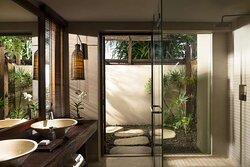 Interior view of bathroom in Ocean Garden Pool Suite with shower and double vanity
