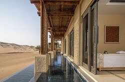 Exterior view of spa treatment room and pool with desert view
