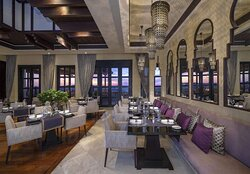 Interior view of Suhail Restaurant dining set-up with sunset view over desert
