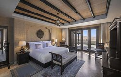 Interior view of bedroom in Three Bedroom Villa with king bed and terrace view