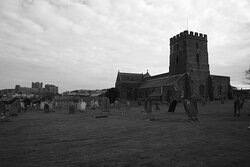 Bamburgh, Northumberland, England, United Kingdom - St Aidan's Church with Bamburgh Castle in the background.