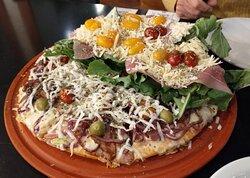 La rúcula fria sin condimentar tirada sobre la pizza