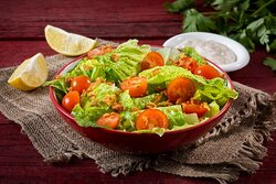 Classic Side Salad- Salad with romaine lettuce, cherry tomatoes, and crunchy onions. Classic Caesar dressing is served on the side.