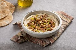 Classic Shawarma Hummus Bowl- Chickpea Hummus Bowl with Chicken Shawarma, Pickles, Garlic Aioli Sauce with Pita Bread Served on the Side.