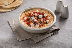 Beef Marinara Hummus- Chickpea Hummus Bowl with Shredded Beef, Roasted Peppers and Onions, Feta Cheese and Herb Marinara Sauce with Pita Bread Served on the Side.