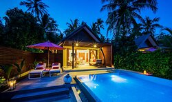 A Beach Pool Villa seen at night, with pool in foreground.