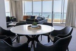 Interior view of dining area and lounge in Three Bedroom Premier Suite with balcony and ocean view
