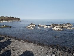 """The southernmost of the twelve recognizable coves on the coast of Santa Tecla is called E' Coculi. """"Coculi"""" or """"Cocole"""" is the equivalent of the Italian """"ciottoli"""" (pebbles). In fact, here the lava cliff is interrupted, and the cove features a wide expanse of pebbles, volcanic rock as well."""