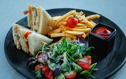 Club Sandwich with chicken breast, bacon, fried egg, fresh vegetables, cheese, potato crisps, sauce