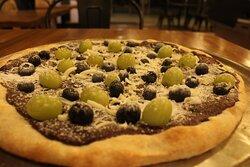 Pizza Dolce, rellena con lagotella, crema de avallenas y chocolate acompañada con frutos del bosque.