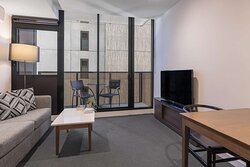 Interior view of lounge and dining area in One Bedroom Deluxe Suite with dining area on balcony