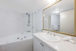 Interior view of bathroom in Two Bedroom Executive Premier Suite with bathtub and vanity