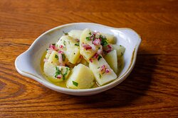 Ensalada de Papa (vg) Boiled potatoes, lightly crushed dressed in a red onion vinaigrette (So2)