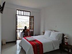 Habitación matrimonial con balcón privado con vista a la ciudad, montañas, baño privado, agua calienta en ducha y grifo.