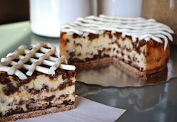 Cinnamon Roll Cheesecake: Breakfast or dessert? A creamy vanilla cheesecake bursting with chunks of cinnamon roll filling on a vanilla wafer crust and drizzled with a cream cheese frosting.