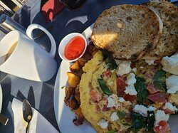 Scrambled eggs with spinach, goat cheese, bacon and tomatoes, home fries and english muffin.