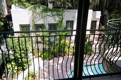 A lovely & intentionally quirky (attempt at quirky anyway) view from the second floor of SSI's Village Inn & Pub showing the uniquely shaped/curved metal protection keeping you from falling off. Notice the protruding little deck to the right. The distant object of the photo is a purposely distorted view of the inner courtyard, not featuring the beautiful pool, but showing the very edge of it while actually showing more of the foliage around it. Very relaxing environment. Recommended.