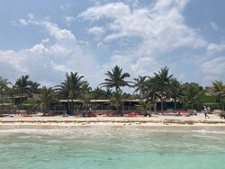 The beach and shade area just outside of Pocna's restaurants, as seen from waist-deep in the ocean