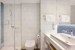 A Holiday Inn Express white tiled bathroom with a walk-in shower.