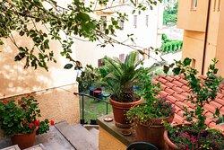 cortile con scalinata che porta al giardino dell'hotel
