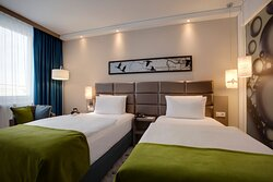 A twin room in warm, earthy tones with free Wi-Fi and a Smart TV.