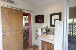 Taaibos Cottage bathroom with shower and a bath.