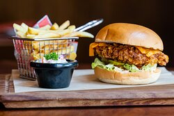 Chipotle Crunchy Chicken Burger  Marinated chicken breast coated in corn flakes, crumb, iceberg, lettuce, gherkins, tomato, chutney