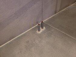 onbeschermde stukjes leiding op de grond tussen de douche en het toilet