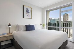 Interior view of bedroom in One Bedroom Suite with city and harbour view