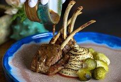 En nuestras novedades de menú: rack de cordero y salsa de vino tinto con almoraduz, puré de papas y coles de Bruselas.