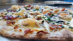 Wood-fired oven pizza with shrimps, pancetta and black garlic made and baked fresh to order!