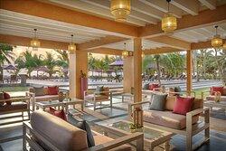 Seating areas on terrace at Miridiya Bar with swimming pool view at sunset