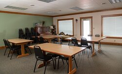 Meeting room available for guest use or daily rentals for non-guests. Seats 36 and has dishes, glassware, silverware, sink, fridge, and microwave. Seating area with couch and piano.