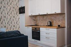 Апартаменты Кристалл Роскошный номер в строгих спокойных тонах.  Спальная зона: двуспальная кровать, диван, шторы Blackout, затемняющие помещение при необходимости, полки настенные, телевизор, телефон. Кухонная зона: гарнитур, раковина, варочная поверхность, стол и стулья, холодильник, чайник, посуда для приготовления пищи. Входная группа: платяной шкаф. Ванная: душевая зона, раковина, зеркало, полотенцесушитель, стиральная машина, унитаз, набор одноразовой косметики.
