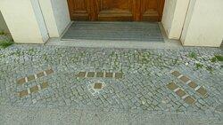 20 Stolpersteine vor einem Haus, welch eine Schande