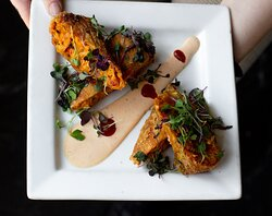 Cajun egg rolls made with blackened chicken breast, black beans, cabbage, bell peppers, and served with spicy ranch.