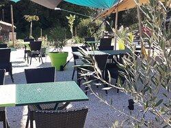 Des tables colorées et des voiles d'ombrages sur la terrasse