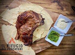 Manzo di Sardegna, solo carne frollata dai 15 ai 45 giorni a Il Rifugio dei Peccatori. Bistecca Fiorentina. Qui accompagnato da salse di nostra produzione: fonduta di pecorino e pesto di rucola.
