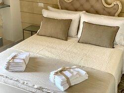 """""""PETRA"""" Room prende ispirazione dalla tipica """"Pietra Leccese"""" che caratterizza l'architettura delpaesaggio Leccese...... il colore neutro della pietraarredano la camera, i dettagli si rifanno all'arte barocca, ed i materiali veri e naturali rendono l'ambiante puro edelegante. È l'opzione ideale per coppie, amici. Le Camere sono dotate di tutti i confort: bagno privato con doccia dotato di set asciugamani, asciugacapelli, climatizzatore (caldo/freddo), TV 32"""", USB for Device,WI-FI gratuita"""
