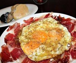 Huevos rotos con jamón ibérico, foie y trufa negra.