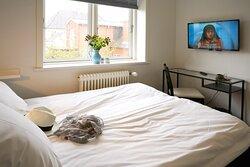 Dobbeltværelse med lille skrivebord og queensize seng.