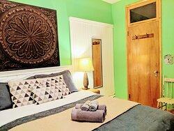Une de nos chambres avec un lit Queen, équipée d'un lavabo.  Les salles de bains sont partagées.  Nous opérons à 50% de capacité, pour respecter les normes sanitaires les plus sévères.