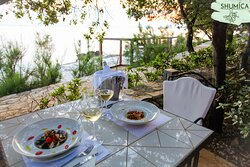 Sunset dinner by the sea accompanied with white Croatian wine