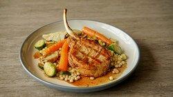 CÔTE DE PORC NAGANO Côte de porc grillée à point, accompagnée d'un couscous israélien, de légumes du moment et d'une sauce au Whisky à l'érable