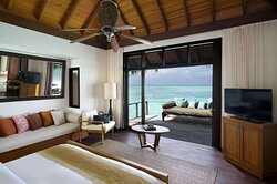 Interior view of bedroom in Superior Over Water Bungalow with lounge seating area and view to daybed on deck and lagoon
